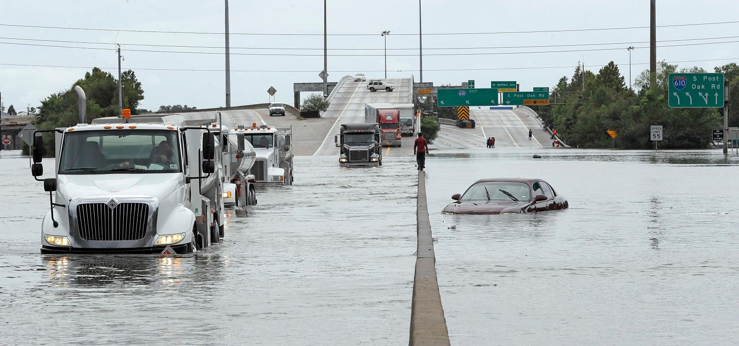 A man walks down the median as trucks navigate floodwaters from Tropical Storm Harvey along Interstate 610 Sunday, Aug. 27, 2017, in Houston, Texas. (AP)
