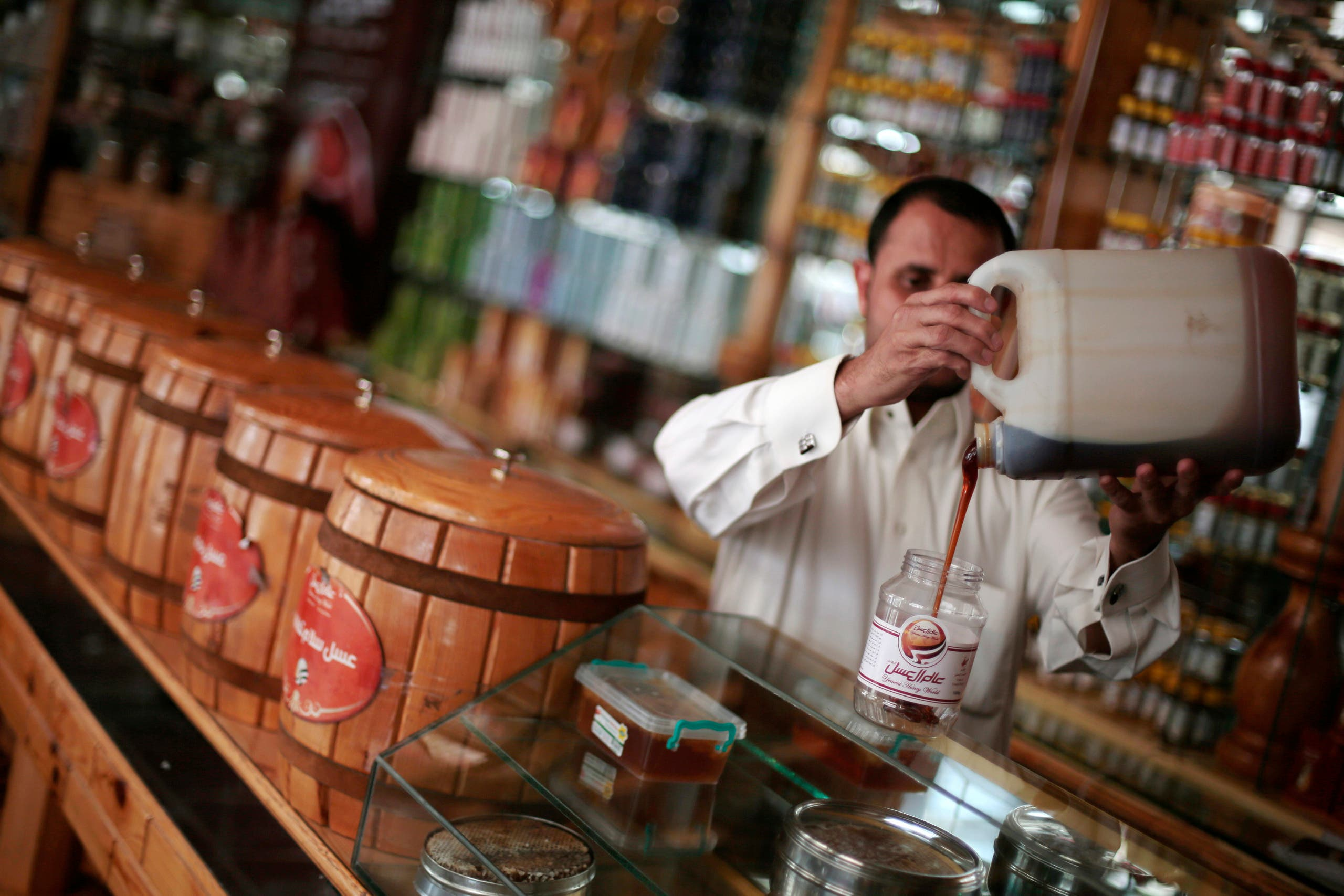 In this Tuesday, Aug. 22, 2017 photo, a Yemeni vendor displays honey for sale in a shop in Sanaa, Yemen.  AP