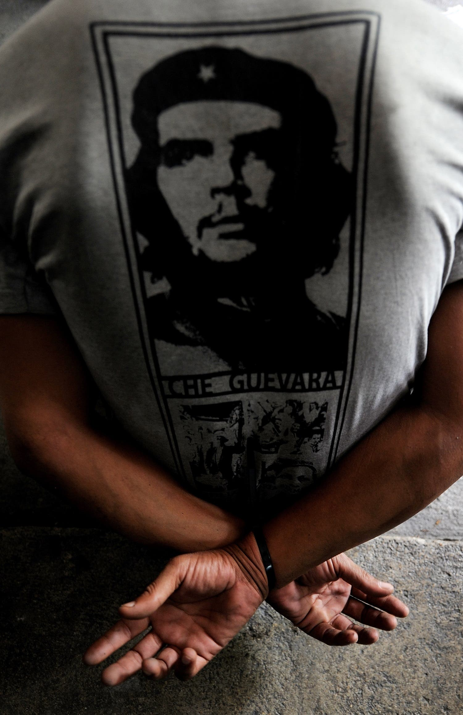 A Red Shirt anti-government protester wearing a t-shirt with a piture of late revolutionary leader Che Guevera is detained by soldiers inside their camp in Bangkok on May 19, 2010. (AFP)