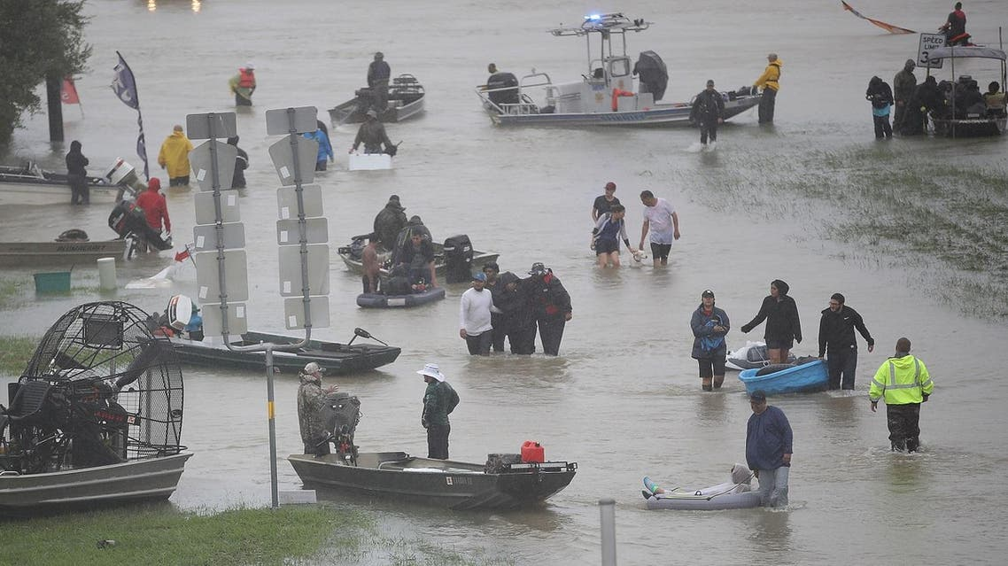 HOUSTON, TX - AUGUST 28: People walk down a flooded street as they evacuate their homes after the area was inundated with flooding from Hurricane Harvey on August 28, 2017 in Houston, Texas. Harvey, which made landfall north of Corpus Christi late Friday evening, is expected to dump upwards to 40 inches of rain in Texas over the next couple of days. Joe Raedle/Getty Images/AFP