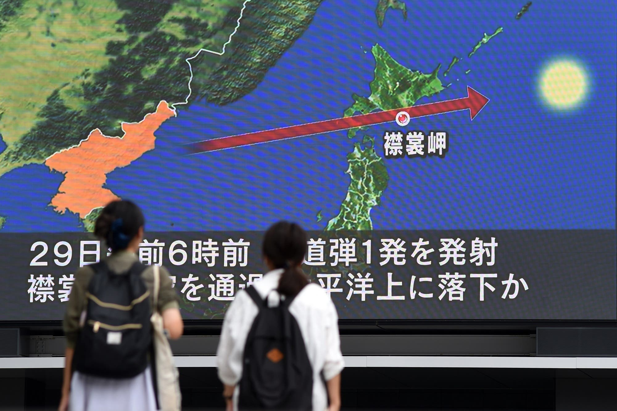 Pedestrians watch the news on a huge screen displaying a map of Japan (R) and the Korean Peninsula, in Tokyo on August 29, 2017, following a North Korean missile test that passed over Japan. (AFP)