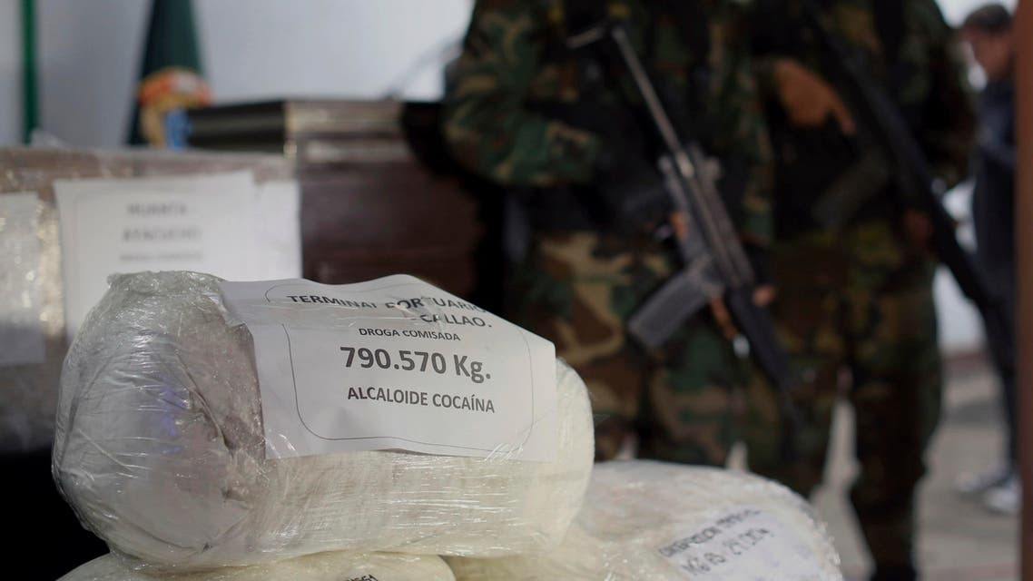 Police officers stand guard next to a bags of seized cocaine during a presentation at a police base in Lima, Peru, Wednesday, June 14, 2017. (AP)