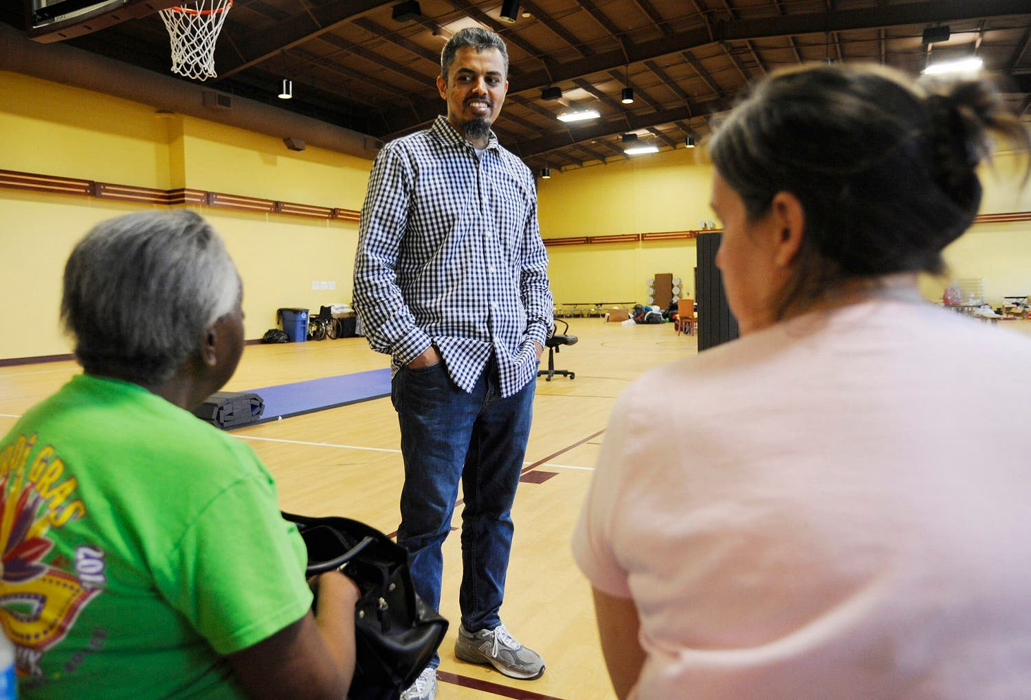 Ayman Kabire, a volunteer at Champions Mosque with the Islamic Society of Greater Houston, talks to evacuees at a mosque that was being used as a shelter. (AP)