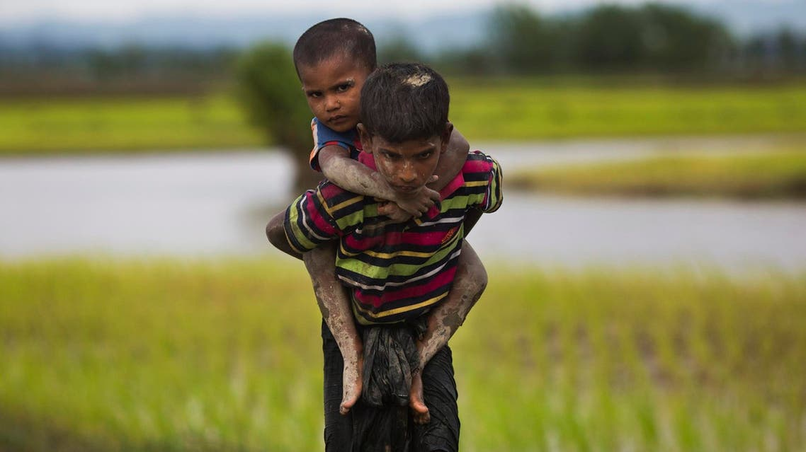 A Rohingya boy from Myanmar carries a child on his back and walks through rice fields after crossing over to the Bangladesh side on Sept. 1, 2017. (AP)