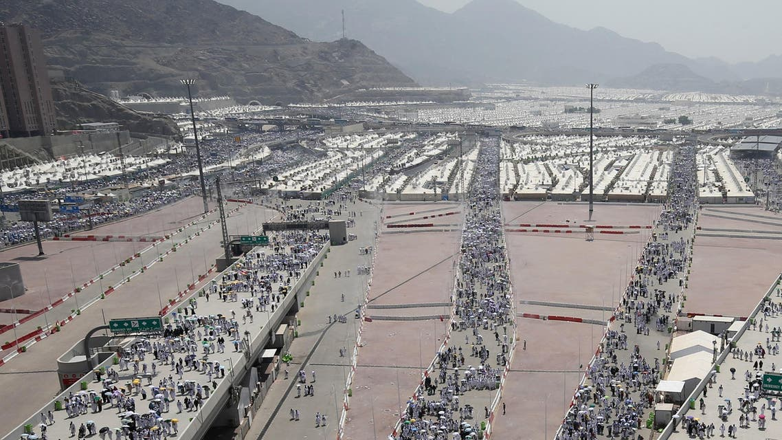 Muslim pilgrims, some holding umbrellas to protect themselves from the sun, head to take part in the symbolic stoning of the devil at the Jamarat Bridge in Mina, near Mecca. (AFP)
