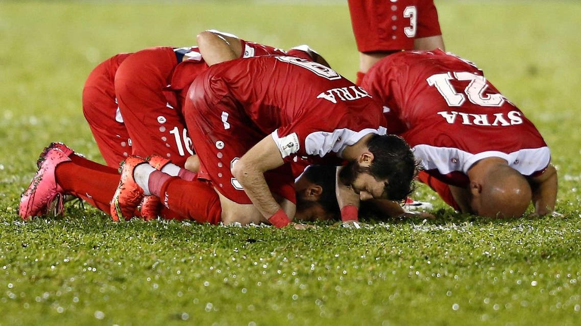 Syrian players celebrate an equalizer against China during World Cup Group A qualifier match in Malacca City, Malaysia, on June 13, 2017. (Reuters)