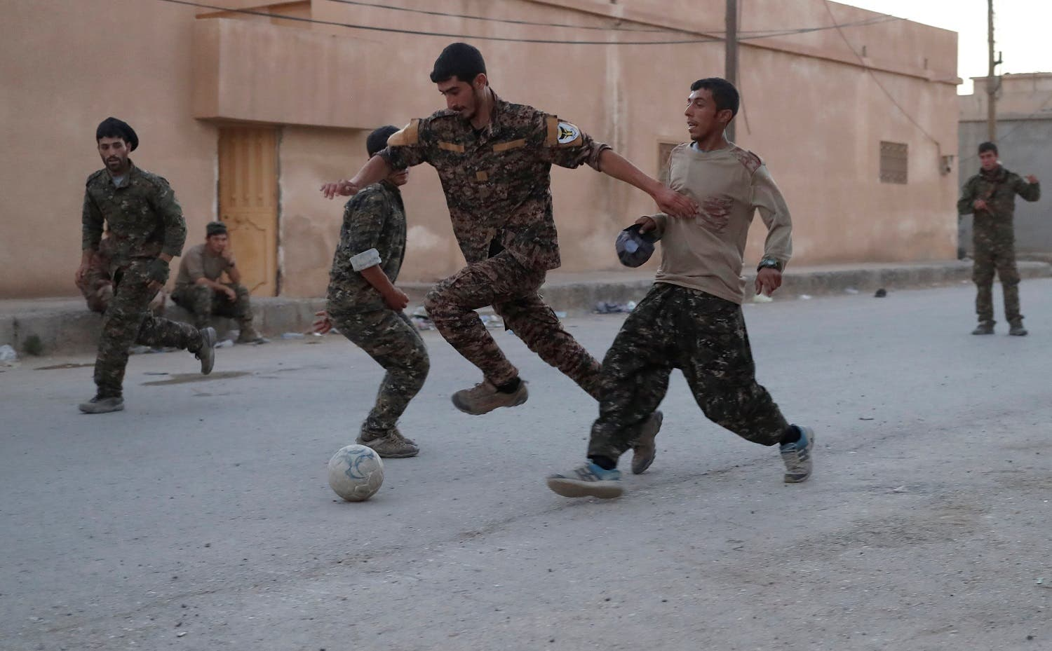 Kurdish fighters from the People's Protection Units (YPG) play football on a street in Raqqa, Syria June 26, 2017. (Reuters)