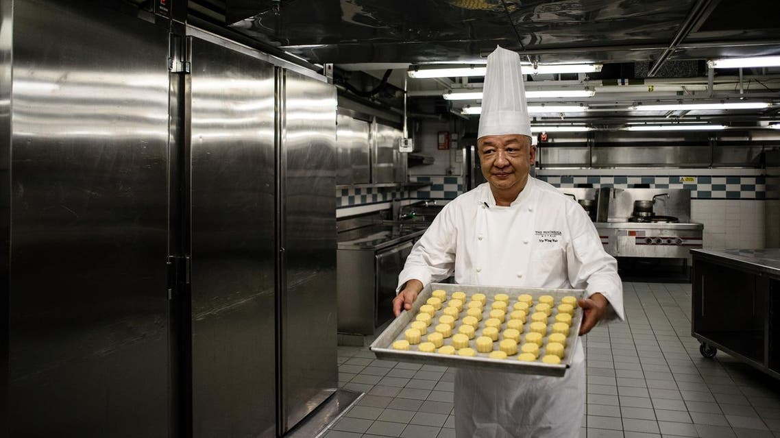 """Chef Yip Wing-wah prepares to oven-bake his signature """"spring moon mini egg custard mooncakes"""" at Hong Kong's Peninsula Hotel. (AFP)"""