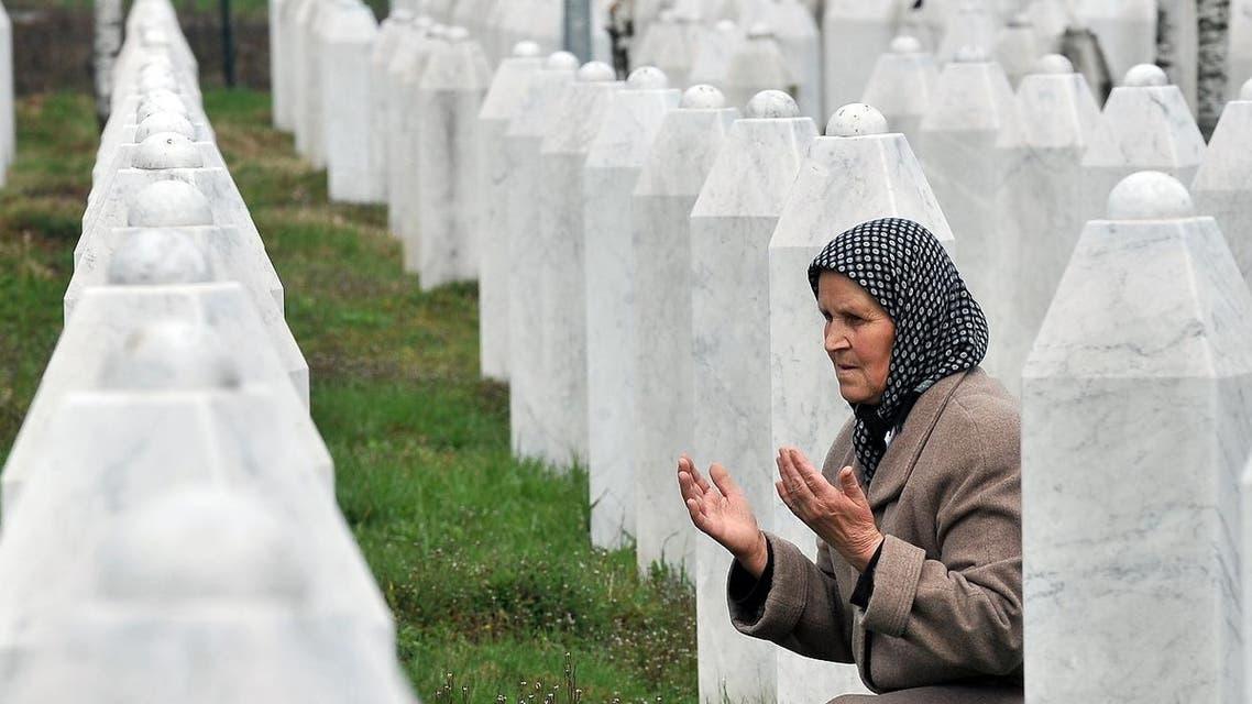 Bida Smajlovic, 64, a survivor of July 1995 massacre in Srebrenica prays by her husband's grave at a memorial center in Potocari, on March 24, 2016. AFP
