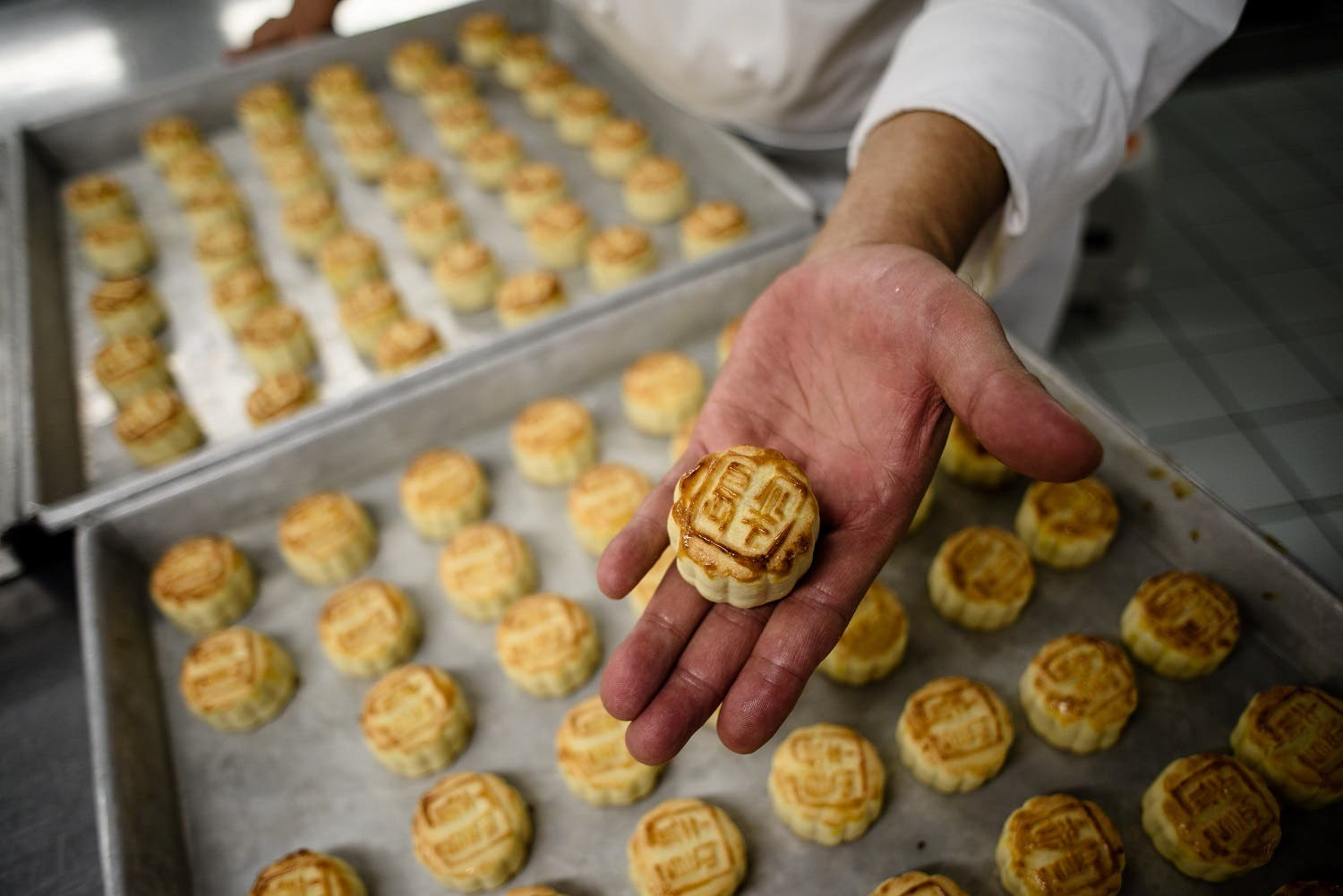 """Chef Yip Wing-wah displays his freshly oven-baked signature """"spring moon mini egg custard mooncakes"""". (AFP)"""
