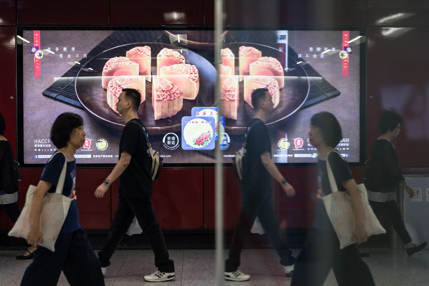 In this picture taken on September 2, 2017, people walk past an advertisement for mooncakes in a train station in Hong Kong. (AFP)