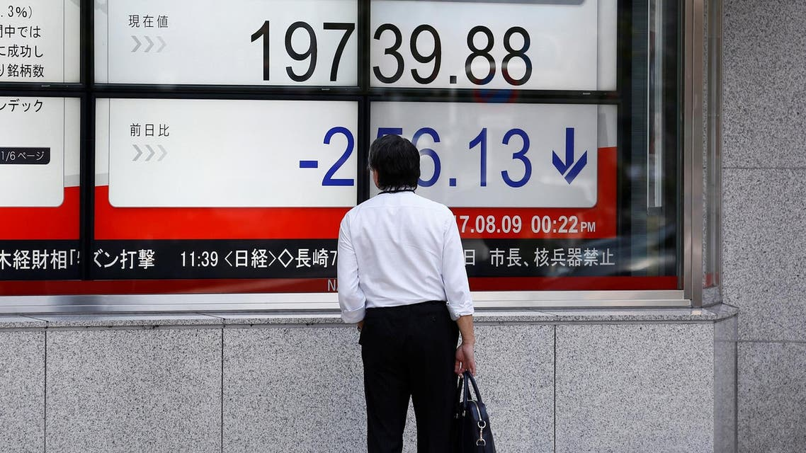 A man looks at an electronic board showing Japan's Nikkei average outside a brokerage at a business district in Tokyo, Japan August 9, 2017. (Reuters)