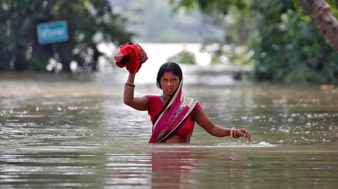 A woman wades through a flooded village in the eastern state of Bihar, India, on August 22, 2017. (Reuters)