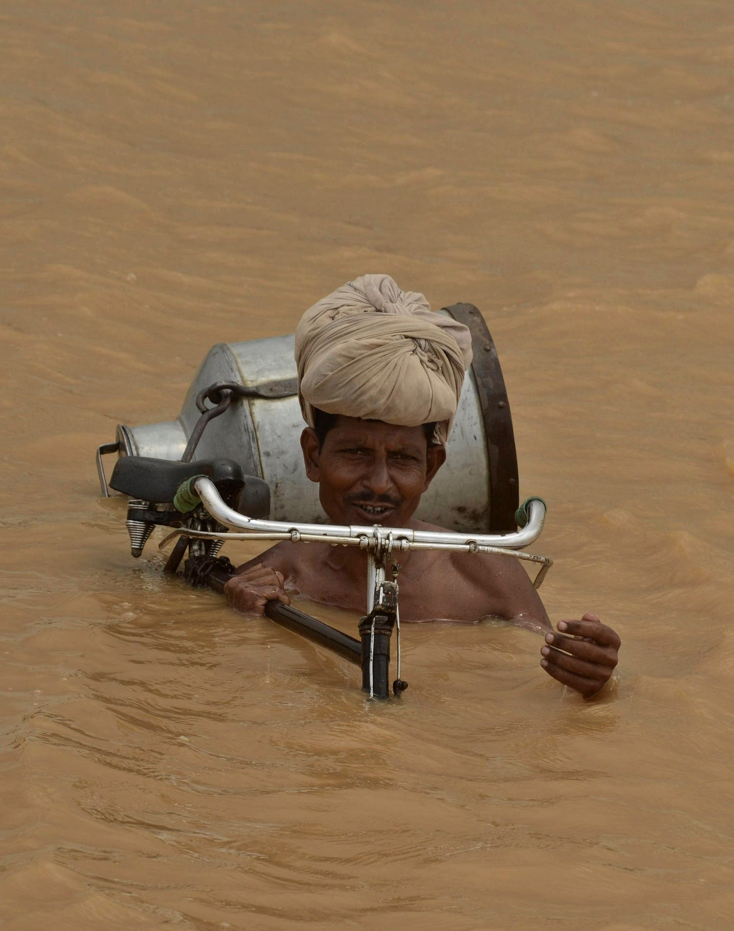 An Indian villager with his bicycle wades through floodwaters at Maner block in Patna district India, on July 31, 2013. (AP)