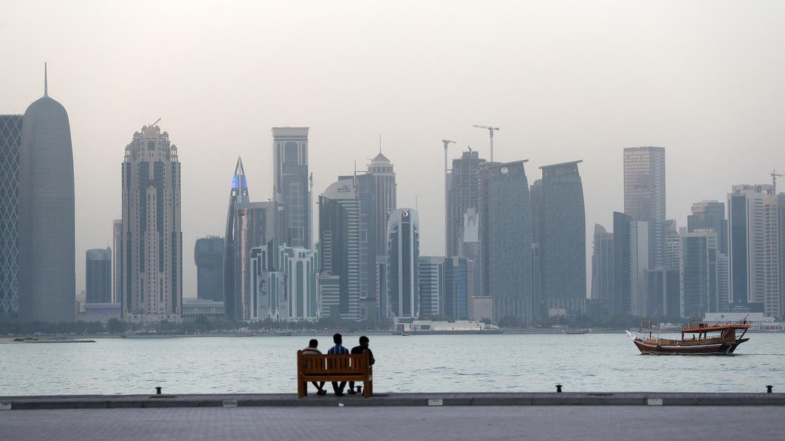 People sit on a bench on the corniche in the Qatari capital Doha on July 2, 2017. AFP