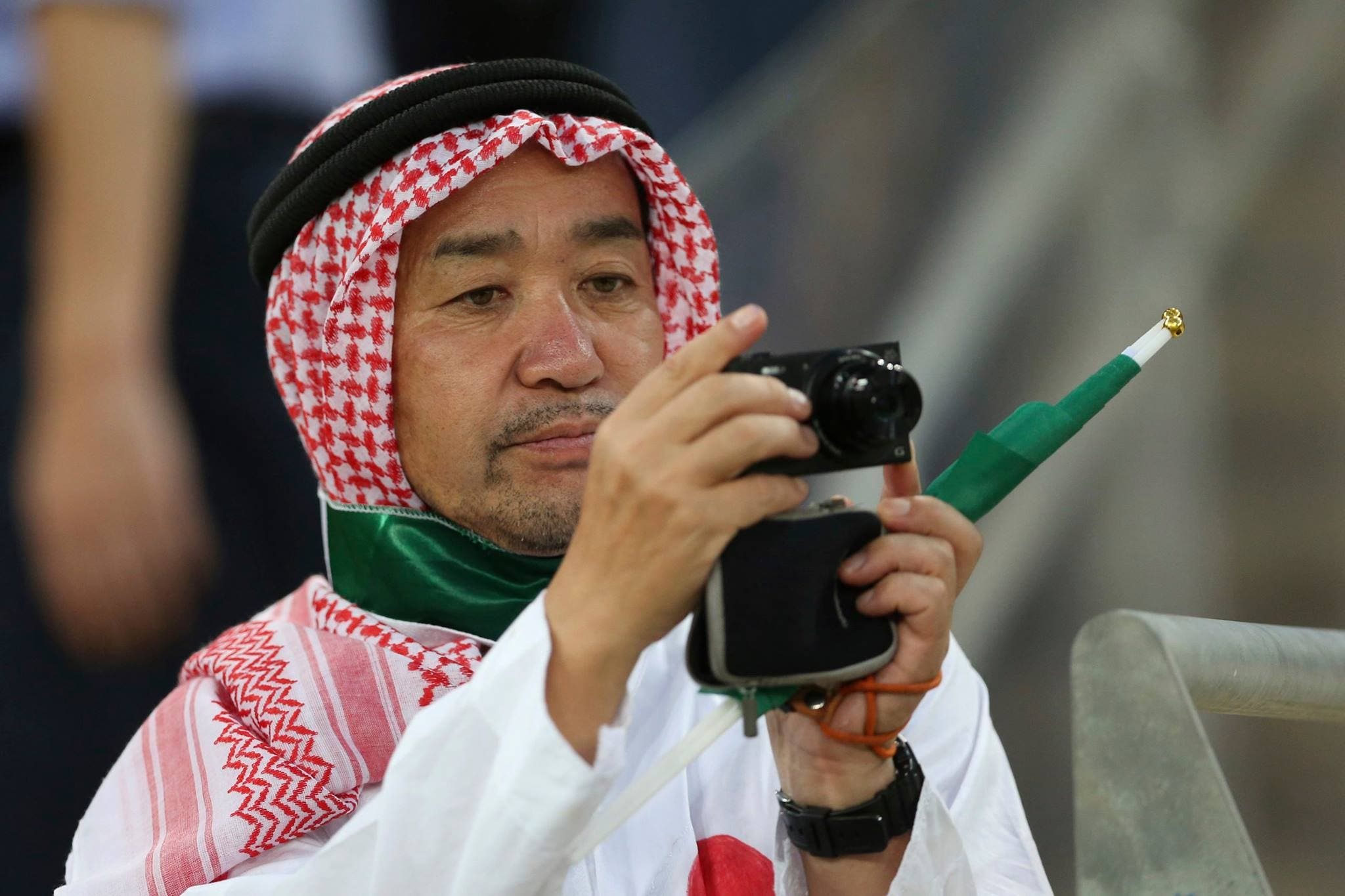 A Japanese fan wears Saudi traditional clothes takes a picture. (AP)
