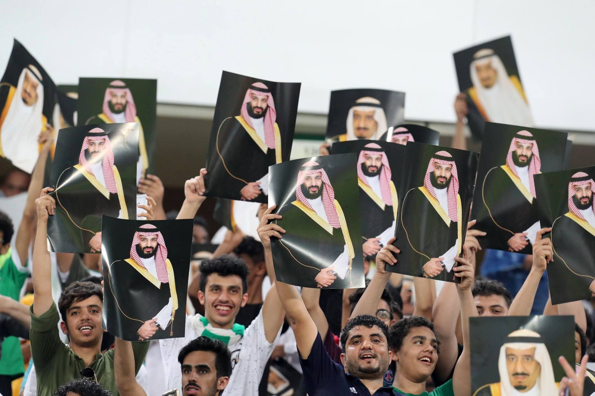 Saudi Arabia fans cheer as they hold up pictures of Saudi King Salman and Saudi Crown Prince and Minister of Defense Mohammed bin Salman. (AP)