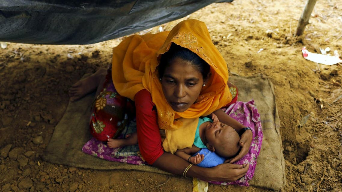 Rohingya refugees from Myanmar's Rakhine state shelter in a makeshift tent after arriving at a refugee camp near the Bangladeshi town of Teknaf on September 5, 2017.