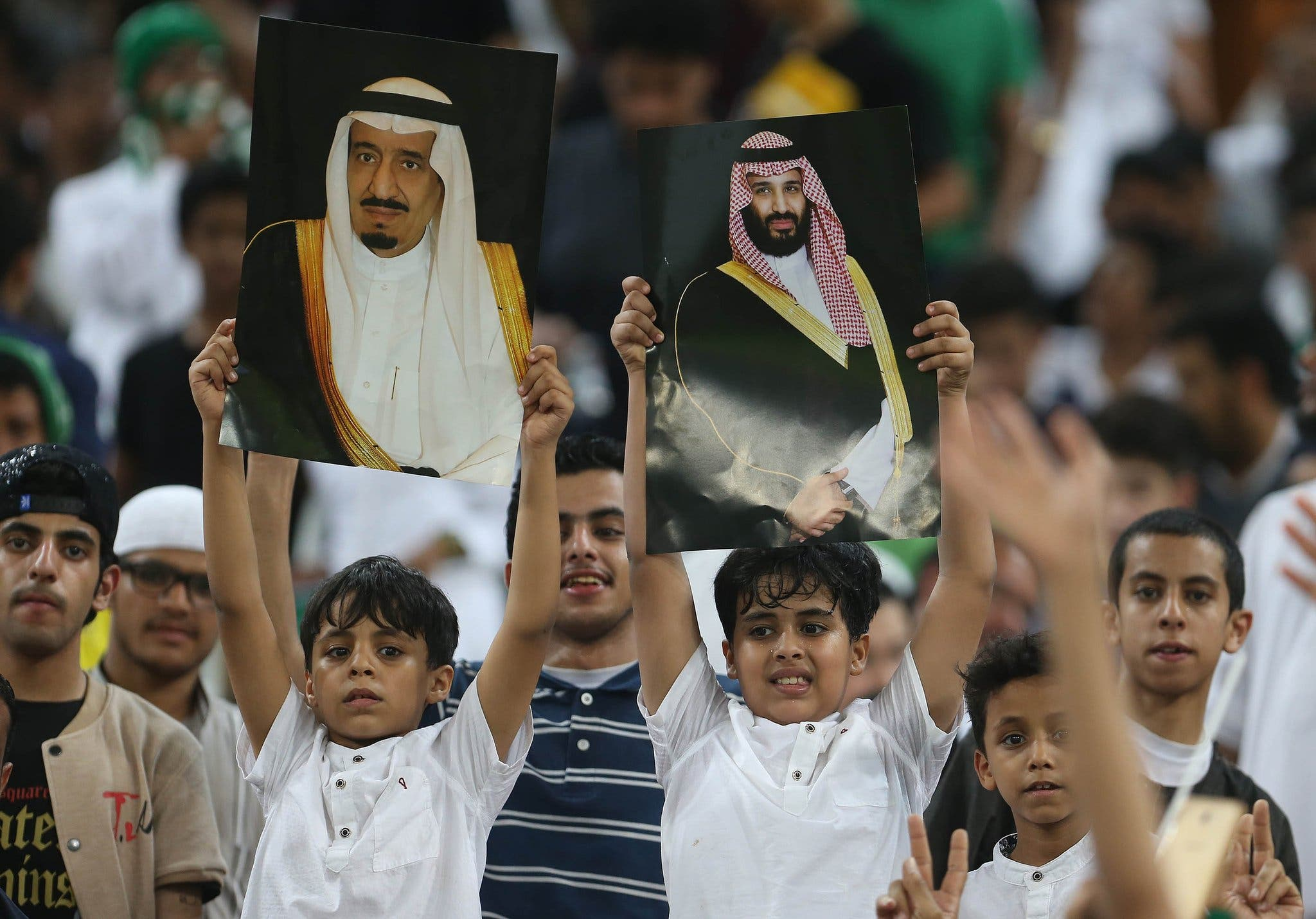 Saudi Arabia's fans hold up portraits of Saudi King Salman and Crown Prince Mohammed bin Salman during the FIFA World Cup 2018 qualification football match between Saudi and Japan at King Abdullah bin Abdulaziz Stadium in Jeddah on September 5, 2017. (AFP)
