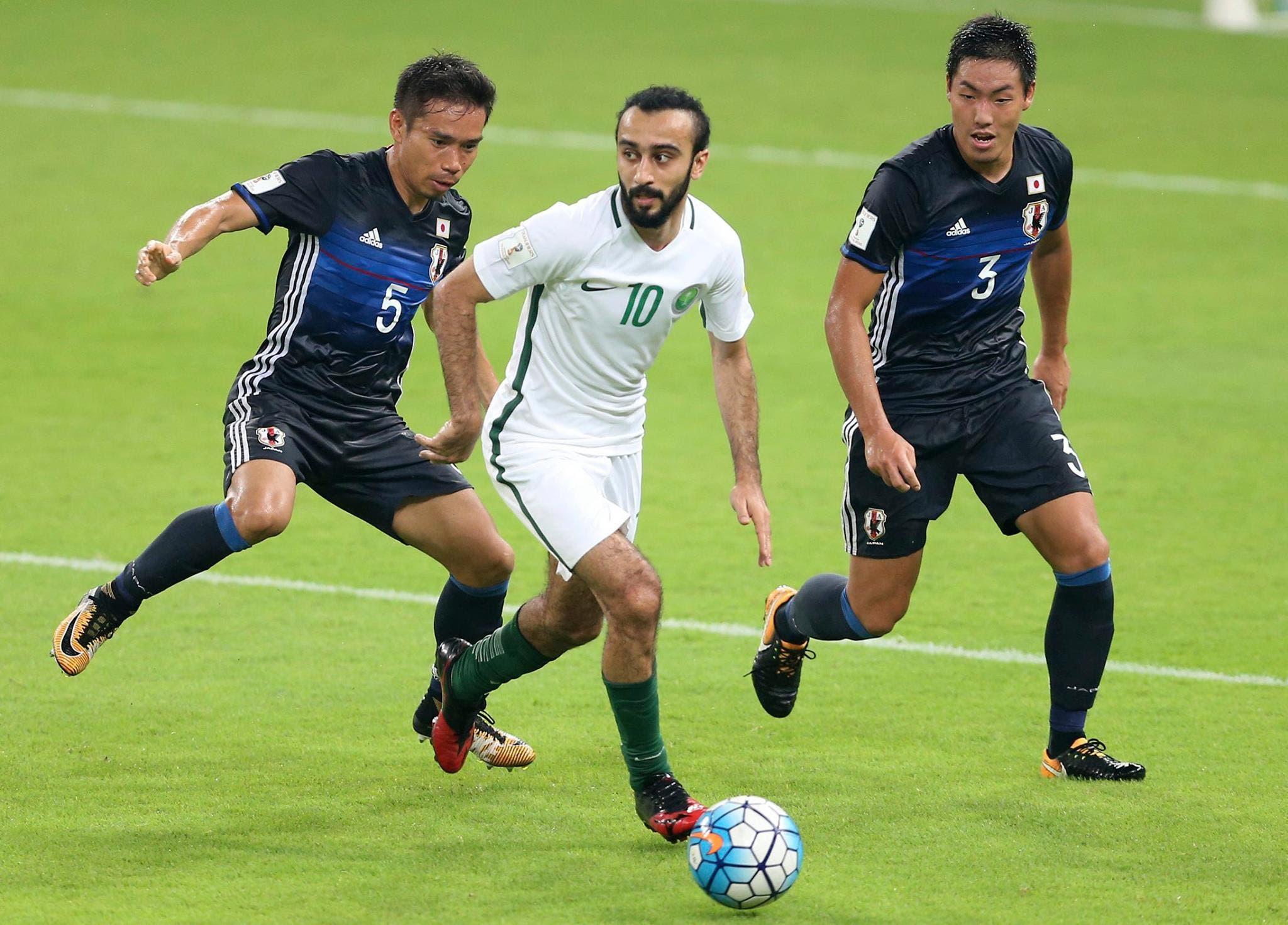 Saudi Arabia's Mohammed Al Sahlawi, center, runs with the ball against Japan's Yuto Nagatomo, left, and Japan's Gen Shoji. (AP)