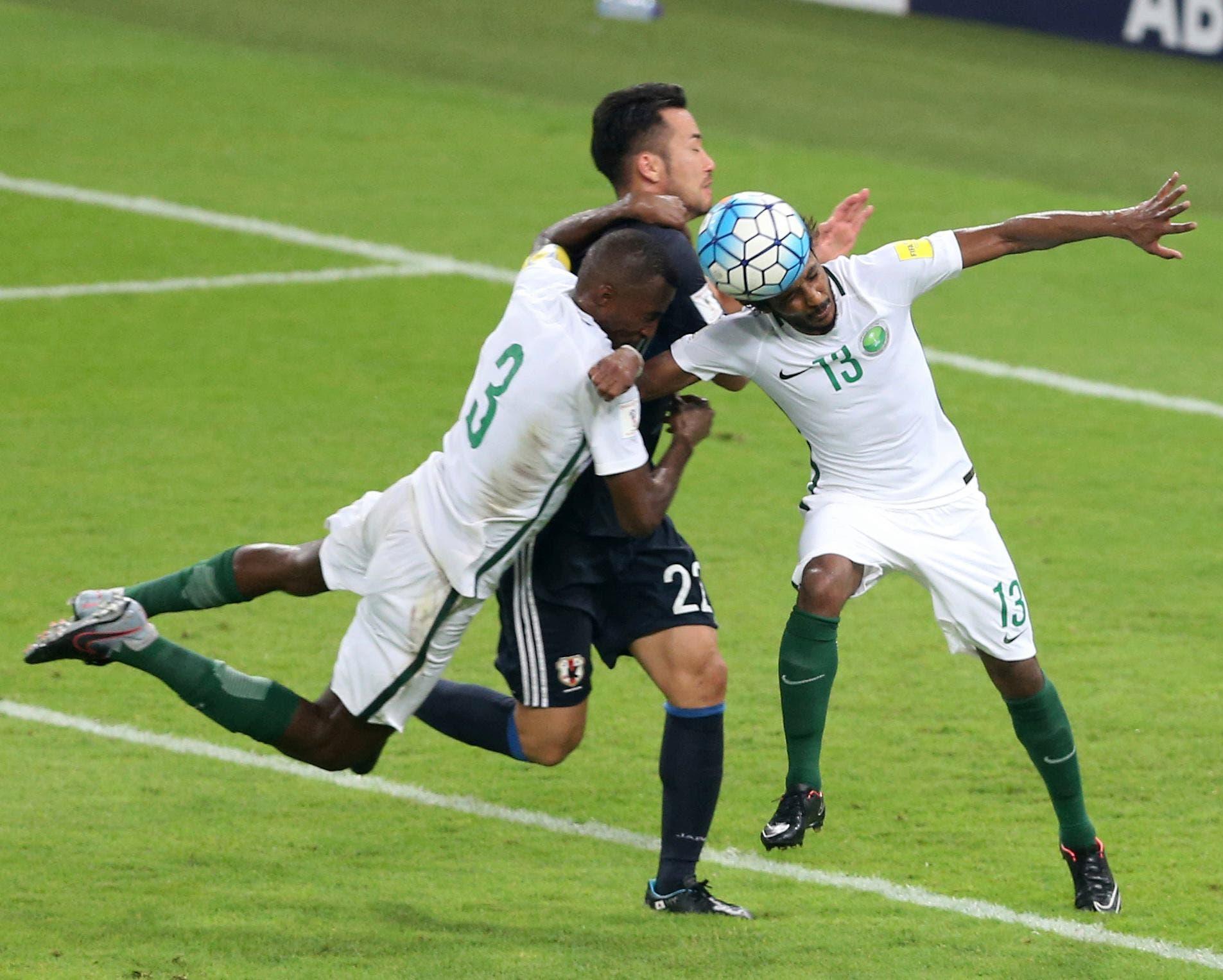 Japan's Maya Yoshida fights for the ball against Saudi Arabia's Osama Hawsawi, left, and Yasir Al Shahrani during the 2018 World Cup group B qualifying soccer match between Saudi Arabia and Japan. (AP)