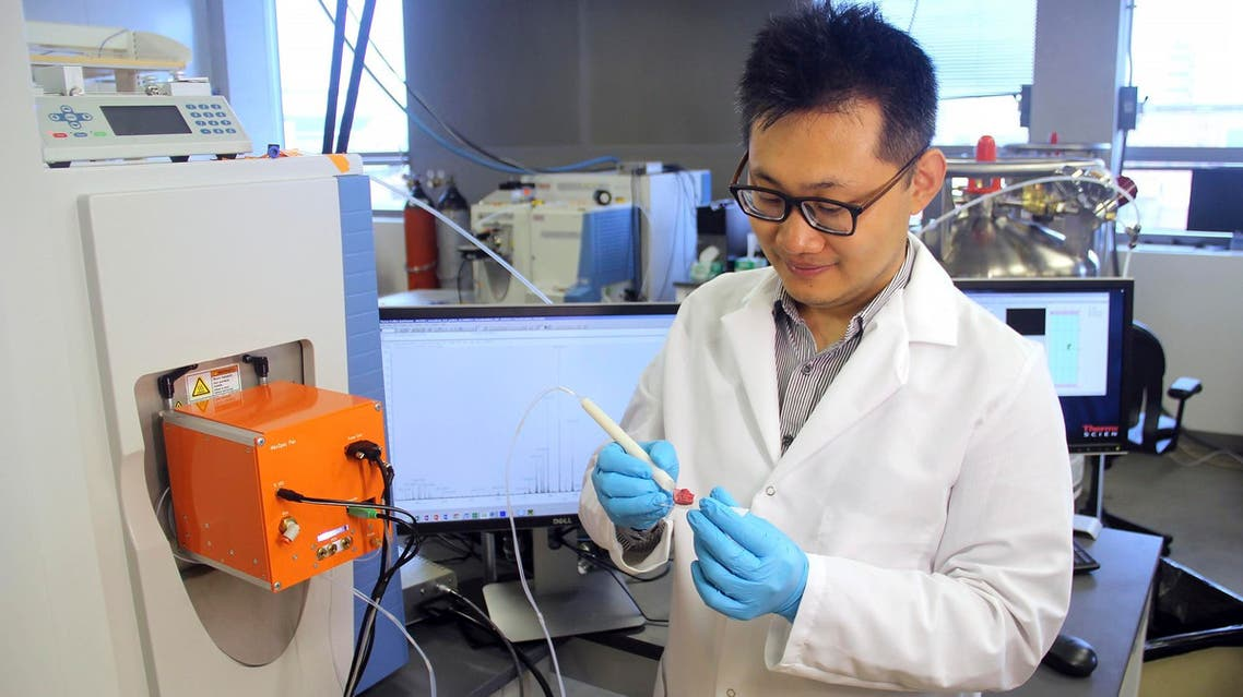 This photo provided by the University of Texas at Austin, shows scientist Jialing Zhang as he demonstrates using the MasSpec Pen to analyze a human tissue sample. (AP)