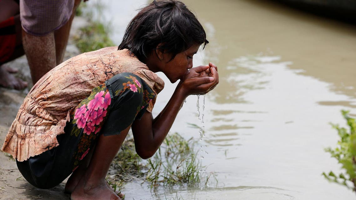 A Rohingya refugee girl drinks river water as she waits for boat to cross the border through Naf river in Maungdaw, Myanmar, September 7, 2017. (Reuters)