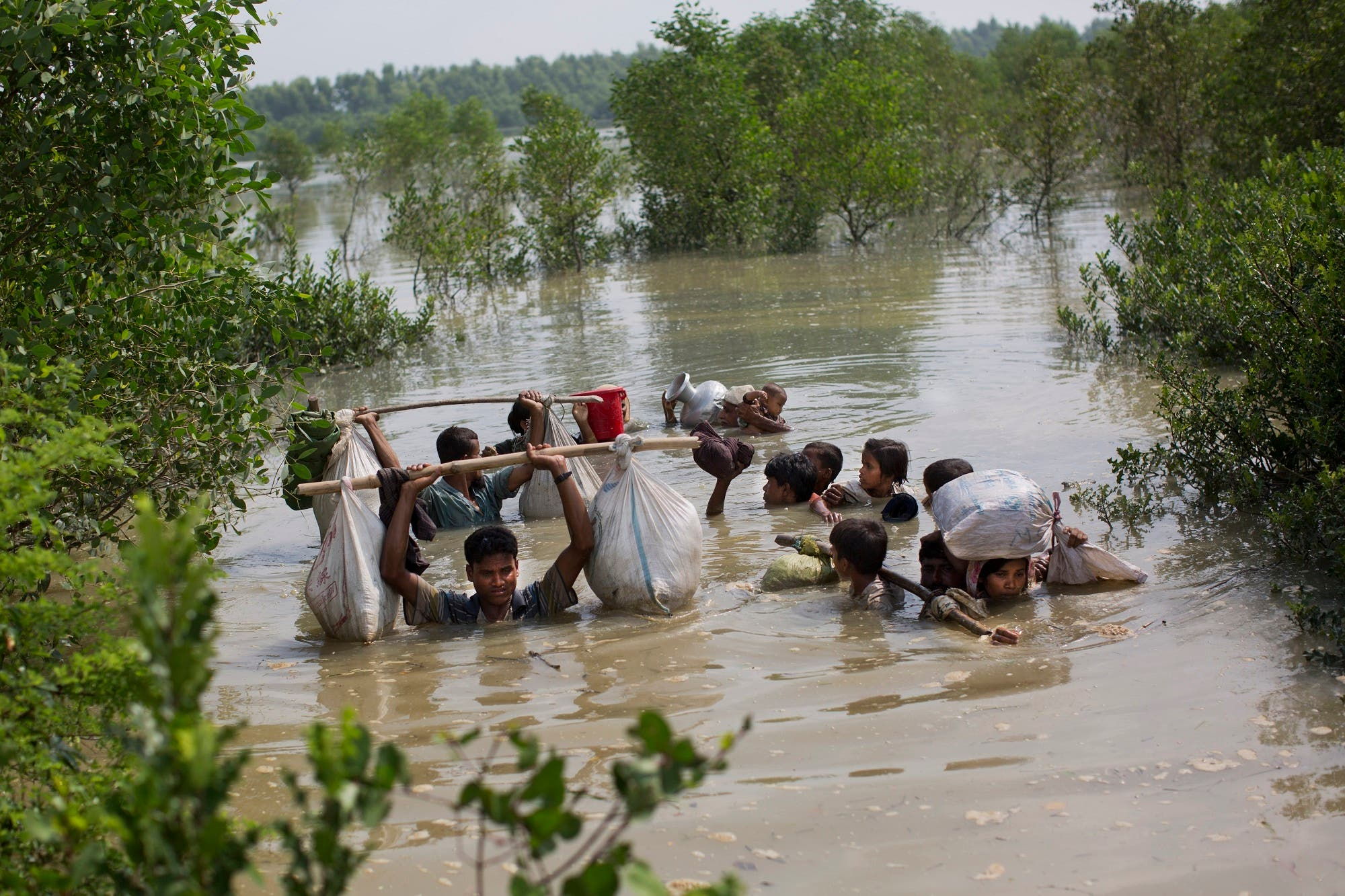 A Rohingya family reaches the Bangladesh border after crossing a creek of the Naf river on the border with Myanmmar, in Cox's Bazar's Teknaf area, on Sept. 5, 2017. (AP)