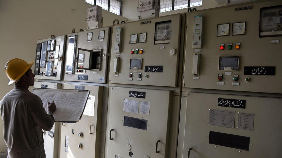 A Pakistani technician notes readings from machinery at a power grid station in Faisalabad. (File photo: AFP)