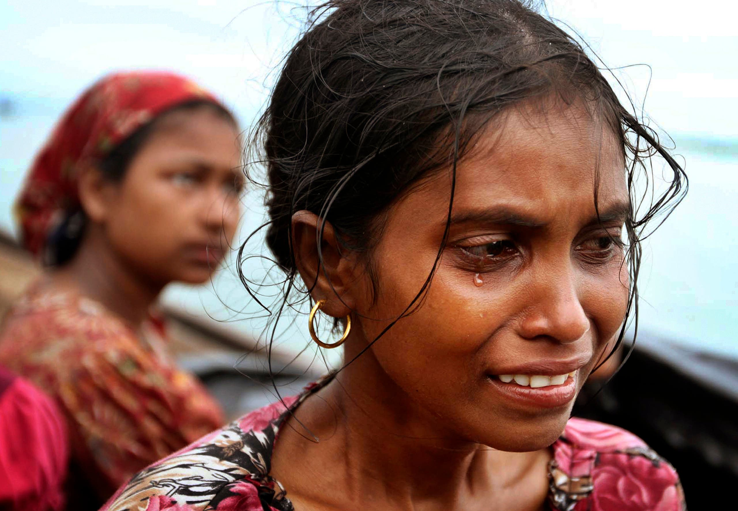 A Rohingya Muslim woman who fled Myanmar to Bangladesh to escape religious violence, cries as she sits in a boat after she and others were intercepted crossing the Naf River by Bangladesh border authorities in Taknaf, Bangladesh, Wednesday, June 13, 2012.