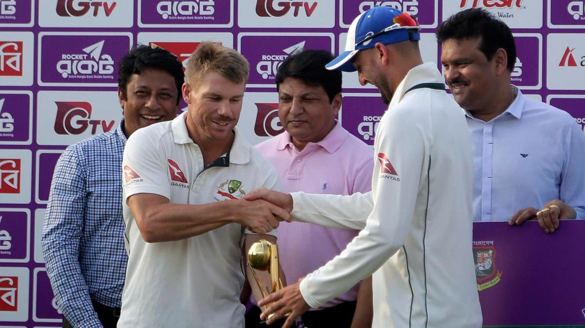 Australia's David Warner (front left), and Nathan Lyon (right), hold the men of the series trophy after the second test cricket match and end of the tournament against Bangladesh in Chittagong on Sept. 7, 2017. (AP)