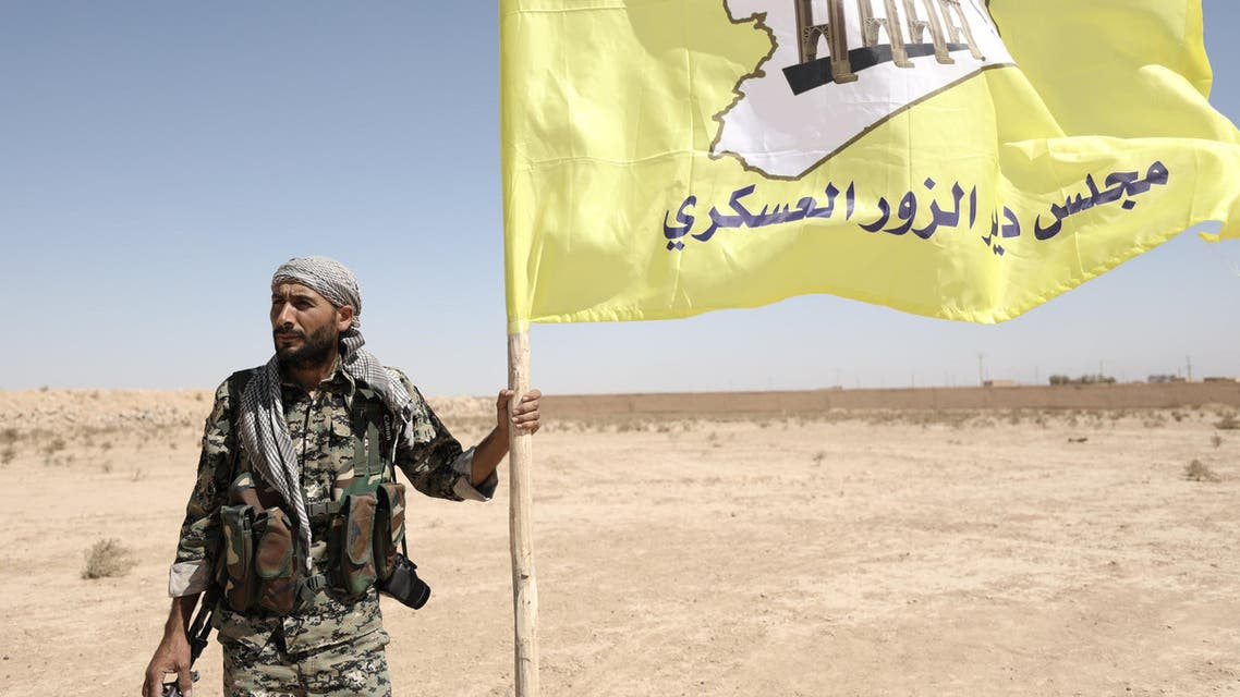 A fighter from Deir al-Zor military council which fights under the Syrian Democratic Forces (SDF) holds the council's flag in the village of Abu Fas, Hasaka province, Syria September 9, 2017. (Reuters)