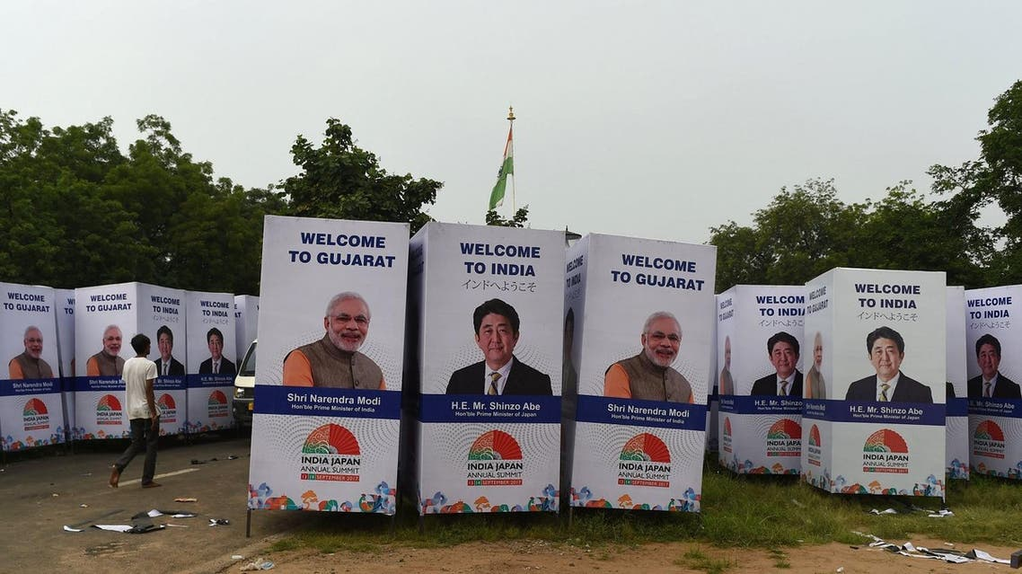 An Indian worker walks past poster with the picture of Japanese Prime Minister Shinzo Abe and his Indian counterpart Narendra Modi, in Ahmedabad on September 10, 2017. (AFP)