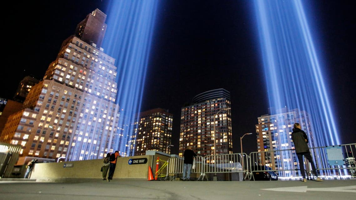 People gather on a rooftop as the 'Tribute in Light' illuminates the night sky, on September 10, 2017 in New York City, on the eve of the anniversary of the September 11, 2001 terror attacks. (AFP)