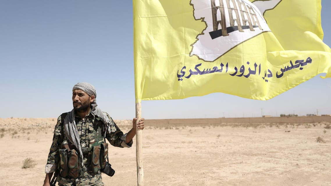 A fighter from Deir al-Zor military council which fights under the Syrian Democratic Forces (SDF) holds the council's flag in the village of Abu Fas, Hasaka province, Syria September 9, 2017. REUTERS/Rodi Said
