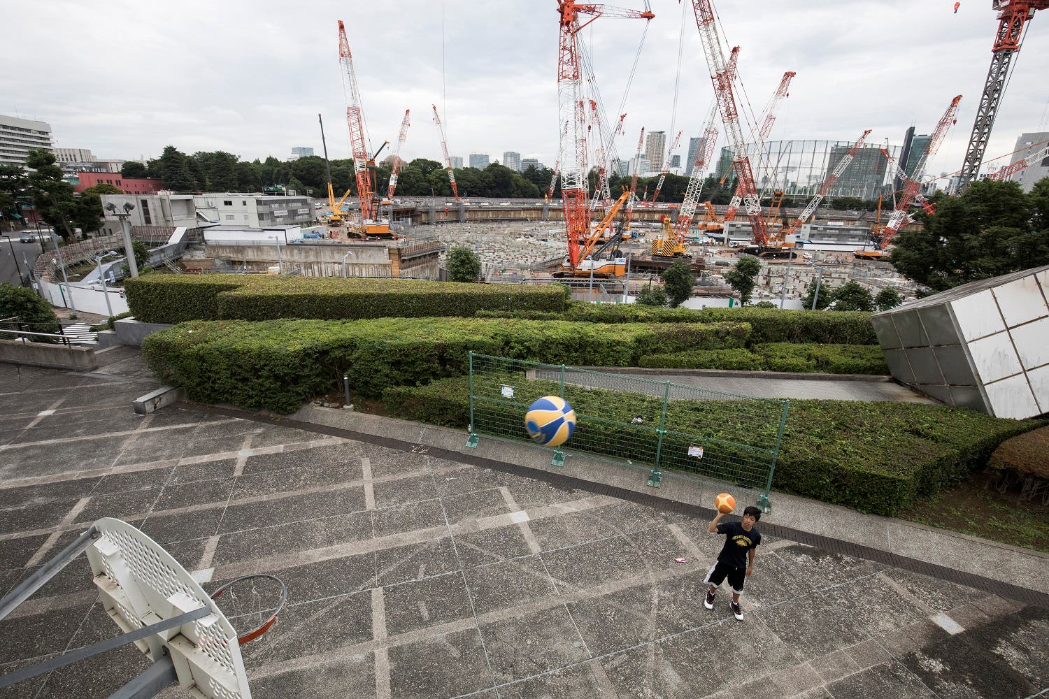A Japanese man plays basketball at the Tokyo metropolitan gymnasium as the construction site for the National Stadium, venue for the upcoming Tokyo 2020 Olympics, is seen in the background in Tokyo on June 30, 2017. The International Olympic Committee (IOC) insisted on June 30 the showpiece venue for the Tokyo 2020 Summer Games would be completed on schedule after a disastrous rollout of the initial plans. (AFP)