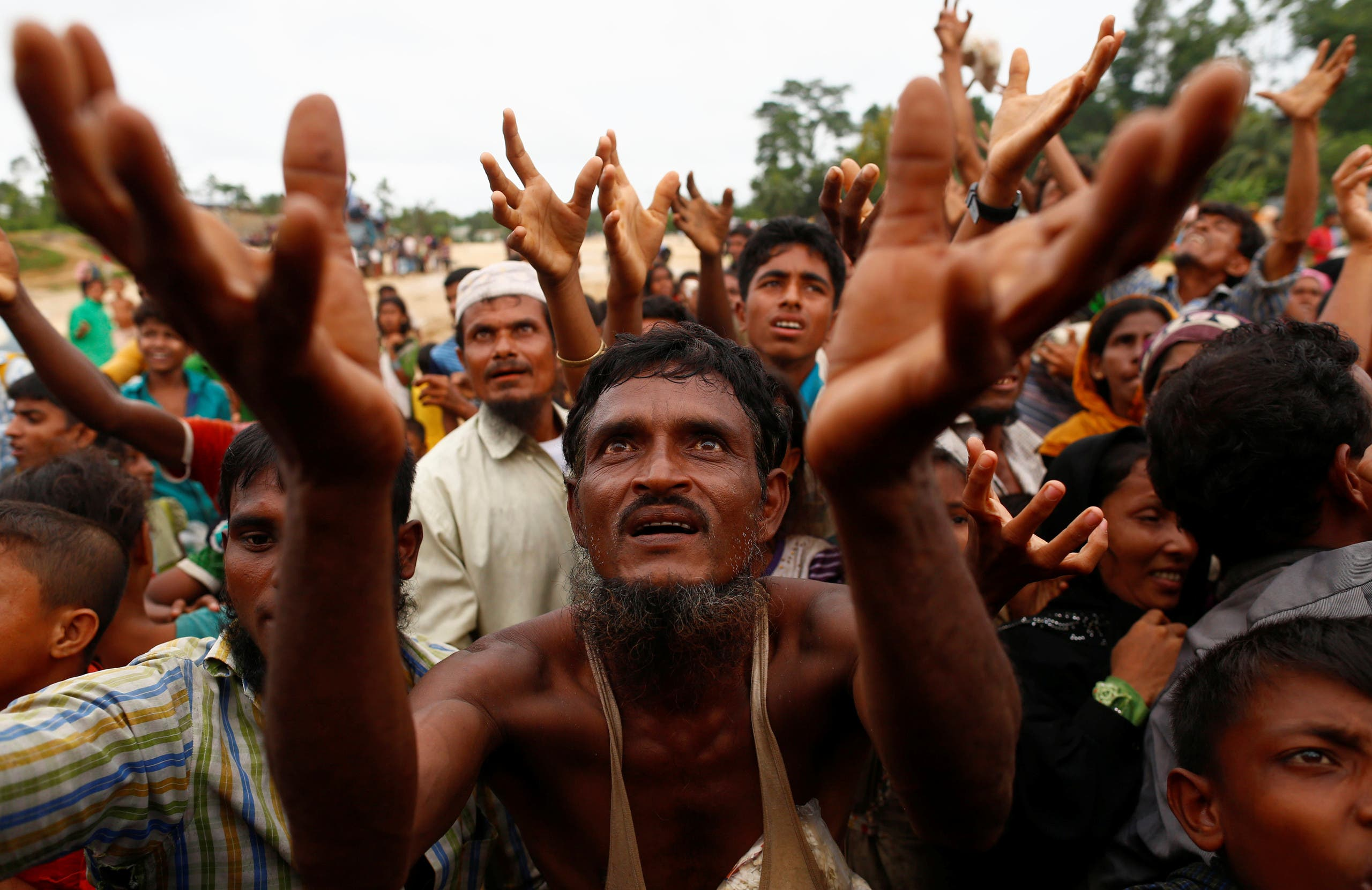 Rohingya refugees stretch their hands to receive food distributed by local organizations in Kutupalong. (Reuters)
