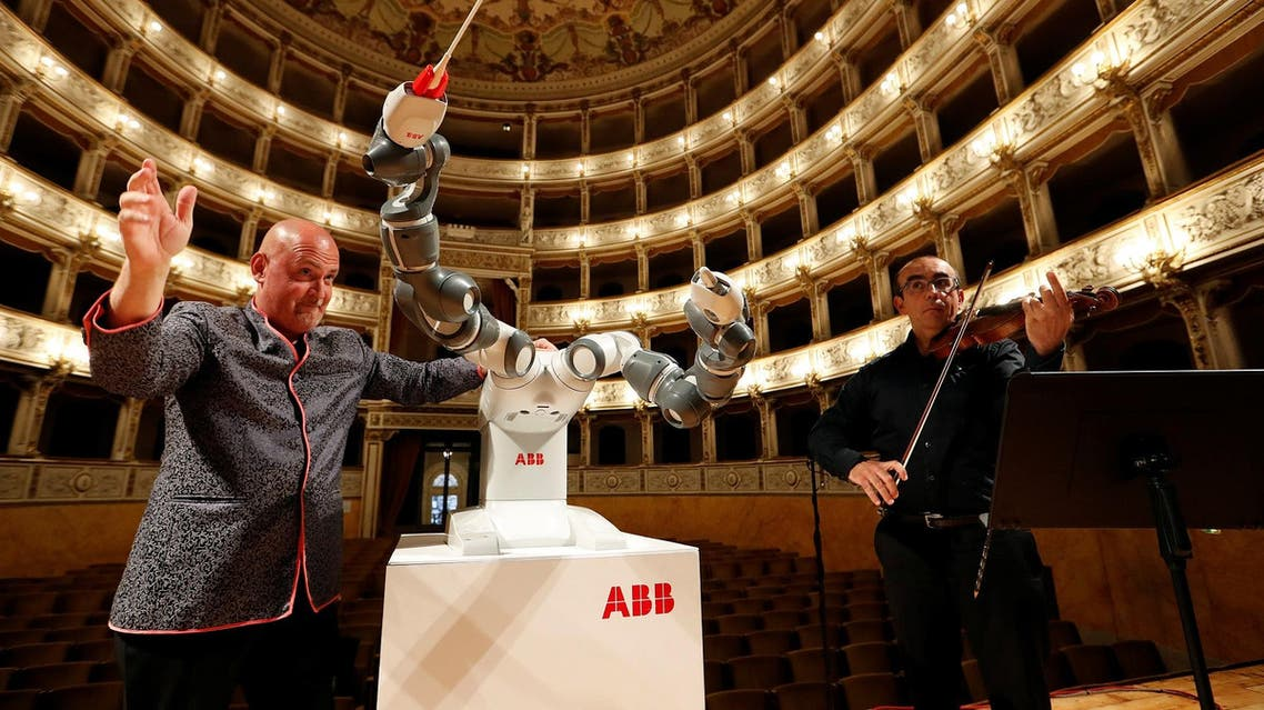 Andrea Colombini (L) trainer of humanoid robot YuMi and orchestra leader and first violinist Claudio Cavalieri during the rehearsal at the Verdi Theatre in Pisa, Italy September 12, 2017. (Reuters)