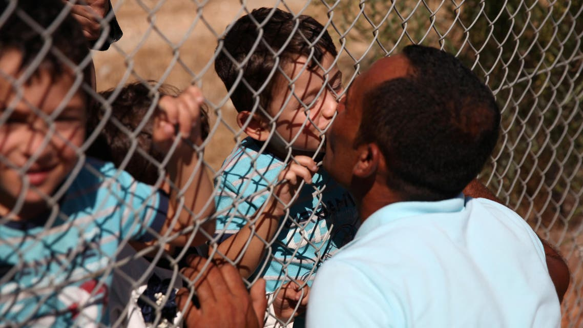 Ammar Hammasho from Syria, who lives in Cyprus, kisses his children who arrived at the refugee camp in Kokkinotrimithia, outside Nicosia, Cyprus, September 10, 2017. (Reuters)
