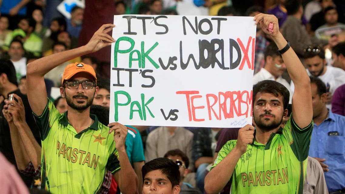 Spectators hold a sign during the final match of World XI cricket series in Lahore, Pakistan September 15, 2017. (Reuters)