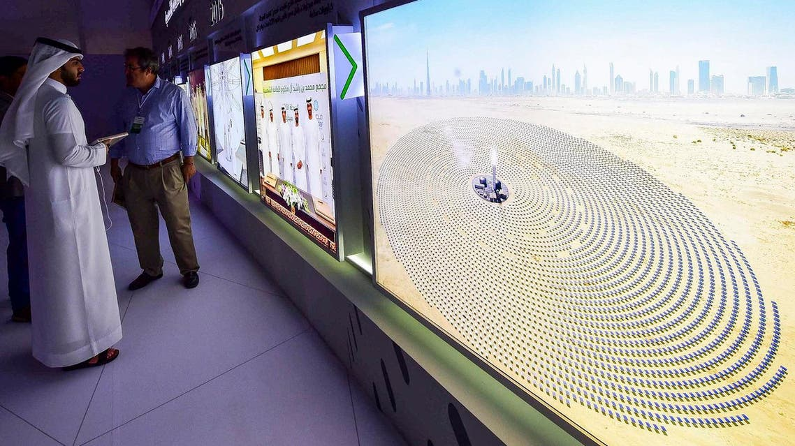 Visitors look at screens displaying images of the Mohammed bin Rashid Al-Maktoum Solar Park on March 20, 2017, at the solar plant in Dubai. (AFP)