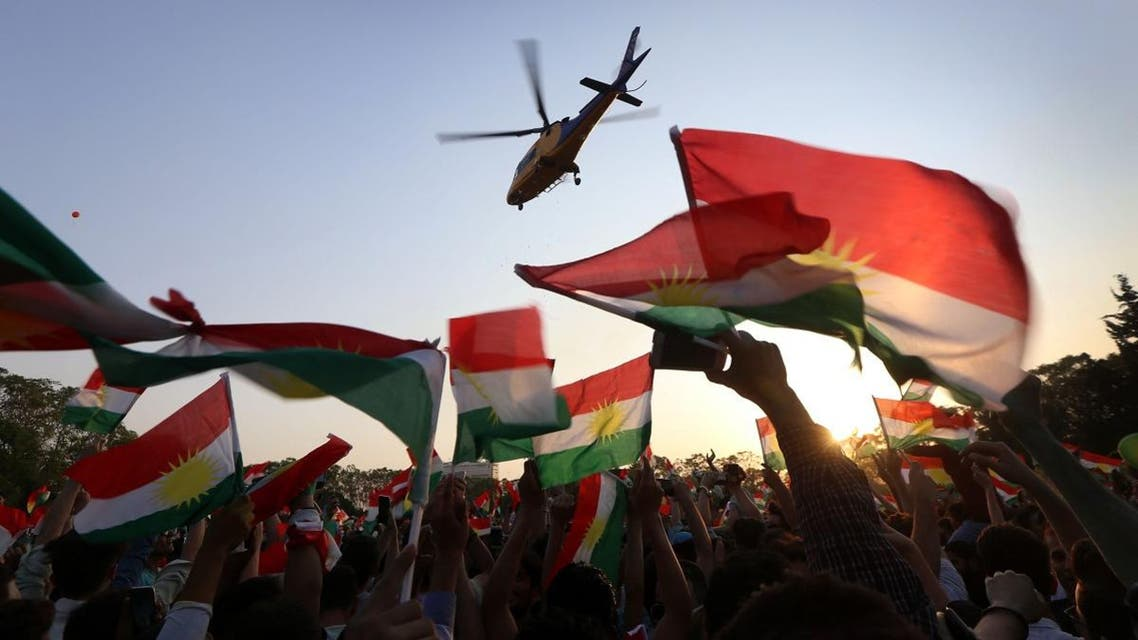 A helicopter flies over Iraqi Kurds gather to urge people to vote in the upcoming independence referendum in Arbil, the capital of the autonomous Kurdish region of northern Iraq. (AFP)