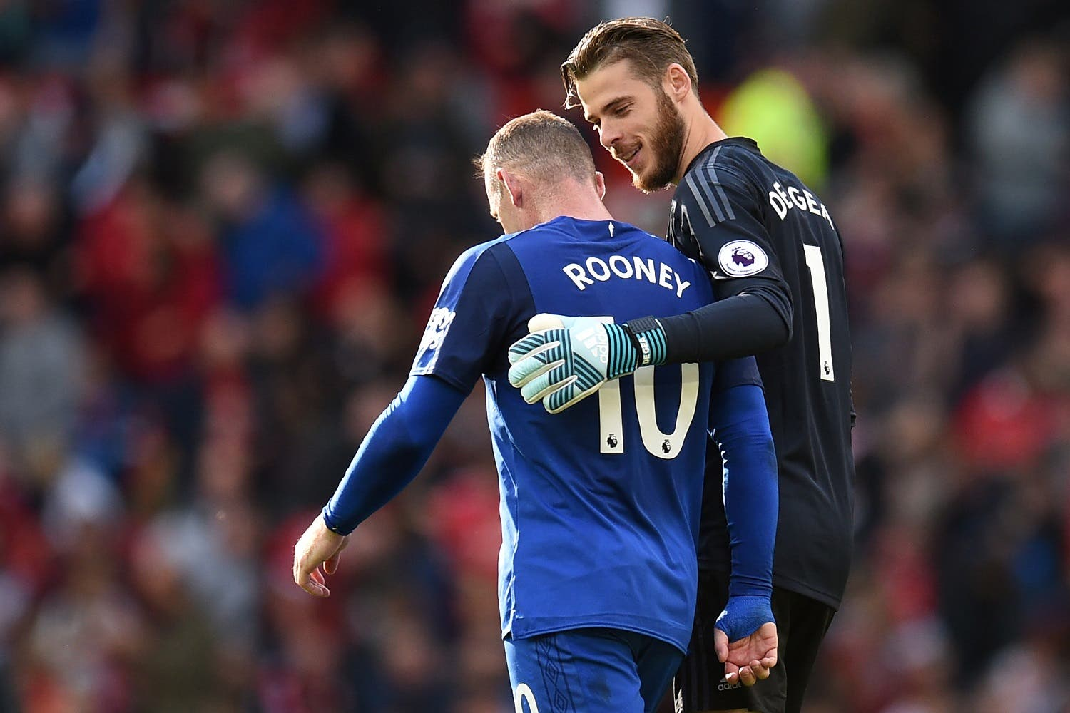 Manchester United's Spanish goalkeeper David de Gea (R) chats with Everton's English striker Wayne Rooney as they walk off the pitch at half time during the English Premier League football match between Manchester United and Everton at Old Trafford in Manchester, north west England, on September 17, 2017. (AFP)