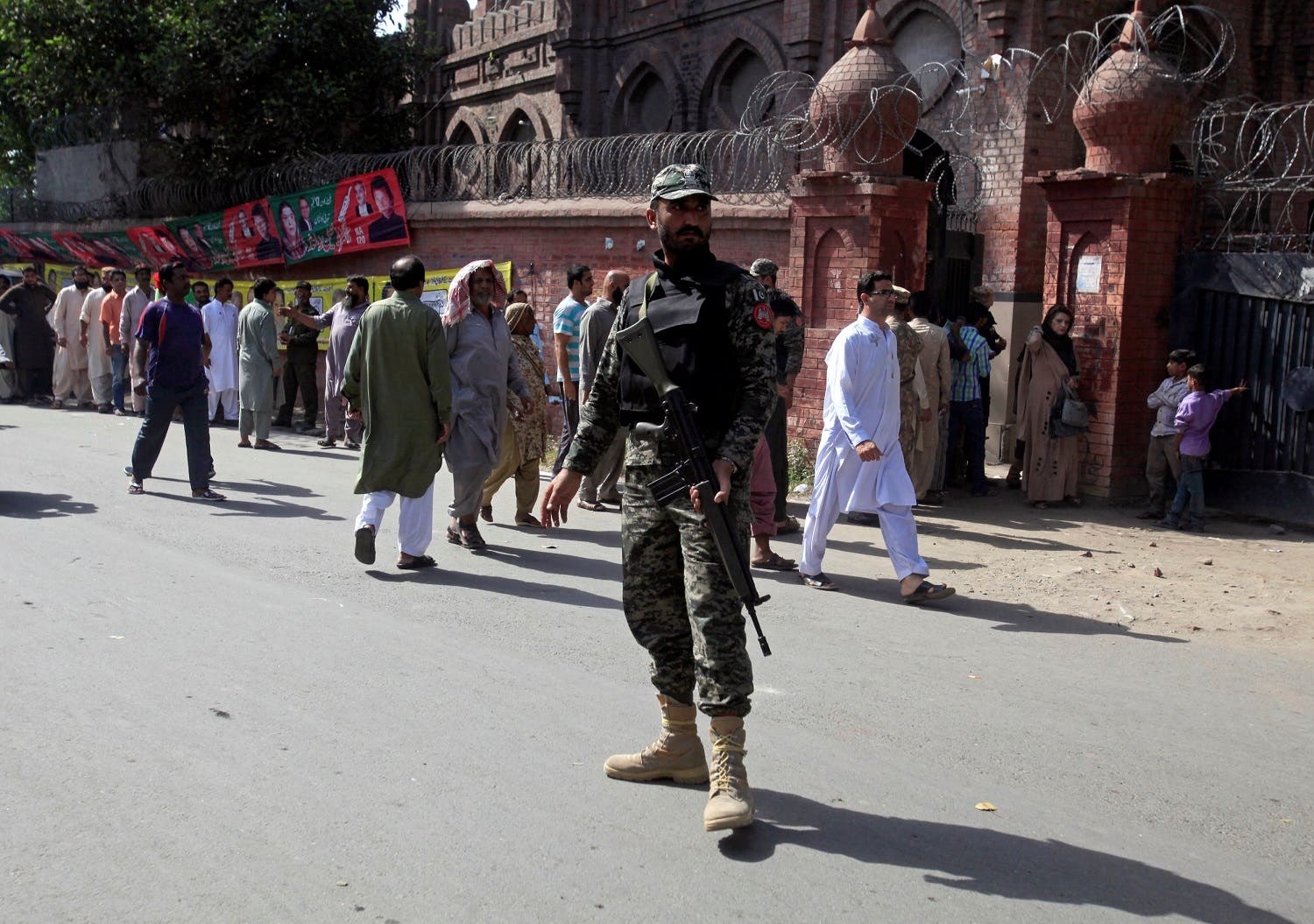 A soldier stands guard as voters stand in line outside a polling station in Lahore, on September 17, 2017. (Reuters)