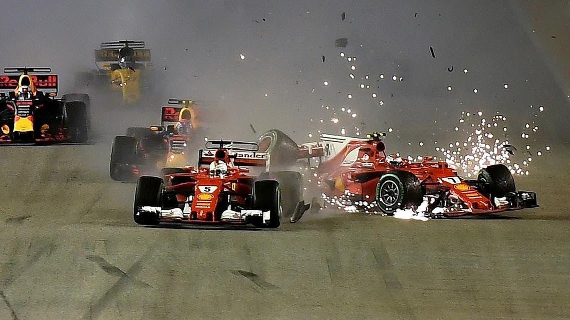 The car of Ferrari's Finnish driver Kimi Raikkonen (R) is seen beside Ferrari's German driver Sebastian Vettel (C) after a crash during the Formula One Singapore Grand Prix in Singapore on September 17, 2017.  MANAN VATSYAYANA / AFP
