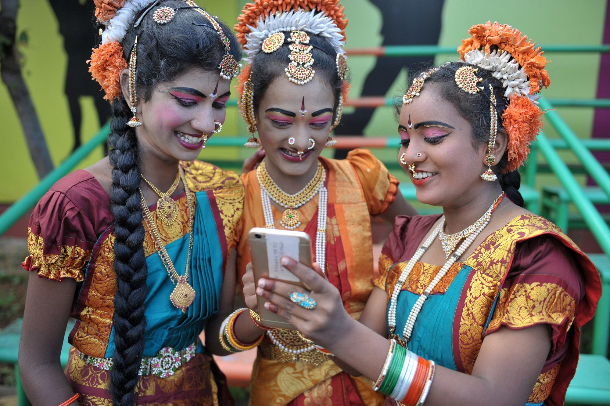 Indian girls look at a mobile phone prior to taking part during Independence Day celebrations in Secunderabad, the twin city of Hyderabad. (File photo: AFP)
