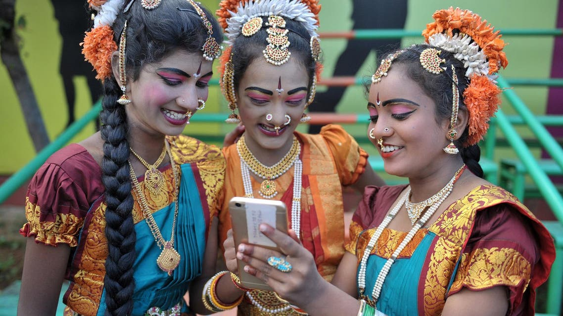 Indian girls look at a mobile phone prior to taking part during Independence Day celebrations in Secunderabad, the twin city of Hyderabad, on August 15, 2017. (AFP)