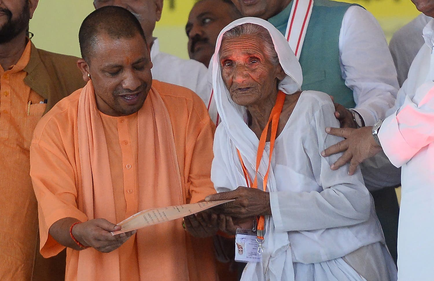The Chief Minister of the Indian state of Uttar Pradesh Yogi Adityanath (L) gives a certificate to a farmer to clear his loans in Allahabad on September 6, 2017. (AFP)