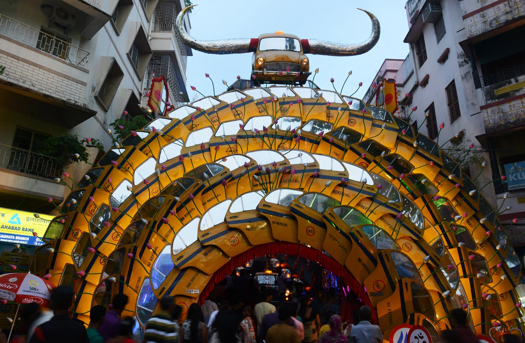 """Indian devotees walk in to worship deity Durga inside the temporary structure called """"pandal"""" decorated with different parts of the city's iconic Ambassador Taxi, in Kolkata on October 9, 2016. (AFP)"""