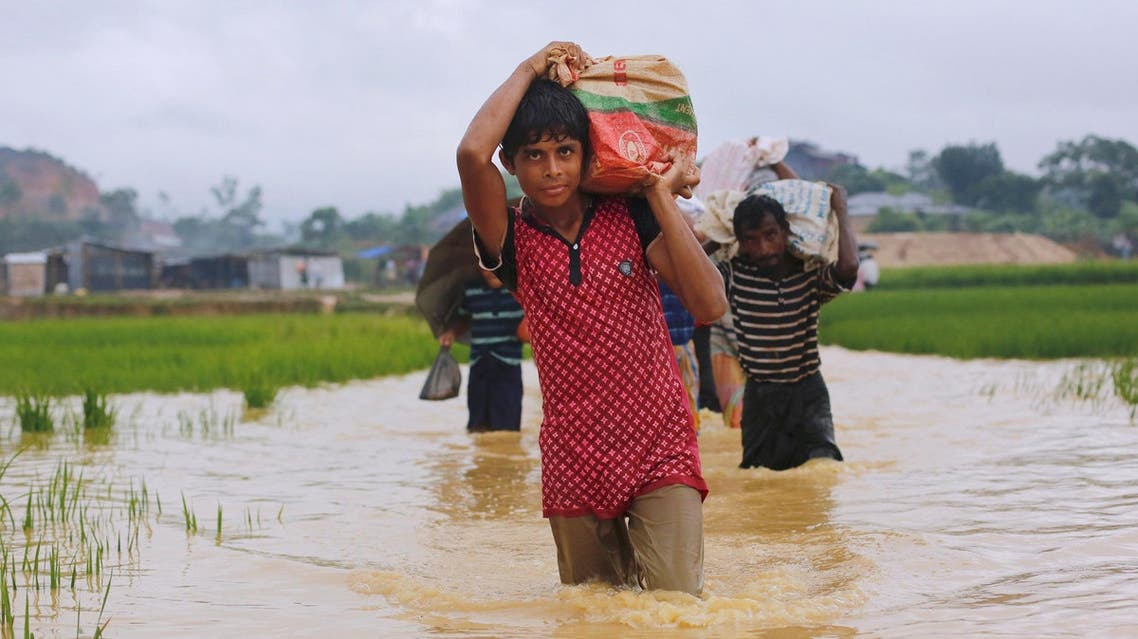 Rohingya refugees carry their belongings as they walk through a flooded pathway at a camp in Cox's Bazar, Bangladesh, September 19, 2017. (Reuters)